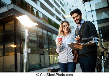 Beautiful young couple walking down the street with tablet