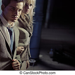 Beautiful young couple walking together in night city