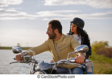 Beautiful young couple with a classic motorcycle