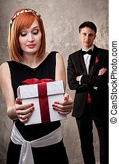 Beautiful young couple with a gift box.