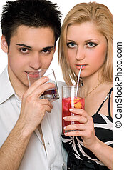 Beautiful young couple with cocktails. Isolated
