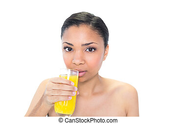 Beautiful young dark haired model drinking orange juice