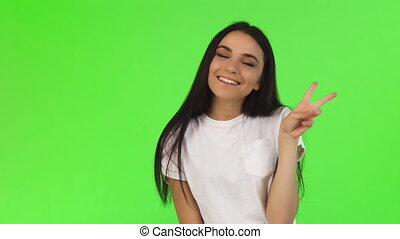 Beautiful young dark haired woman smiling showing peace sign
