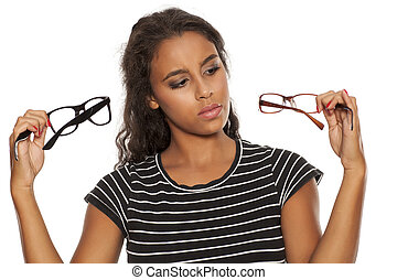 dark skinned woman compare a pair of eyeglasses