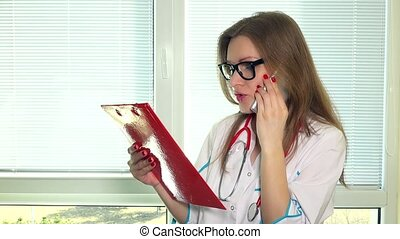 Beautiful young doctor with file folder talking on cell phone with her patient