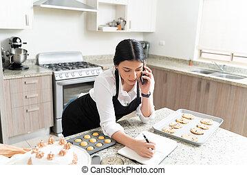 Beautiful Young Entrepreneur Noting Order At Home