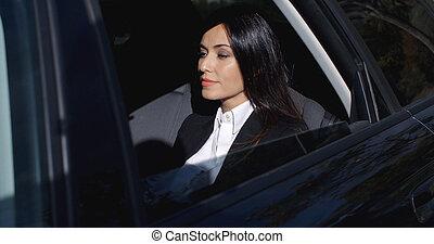 Beautiful young executive sitting in limousine - Beautiful...