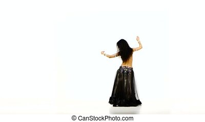 Beautiful young exotic belly dancer with long dark hair in unusual suit dancing, wave of hair, on white