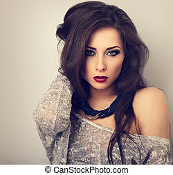 Beautiful young expressive make-up model posing in grey blouse with modern necklace on the neck. Long hairstyle and red lipstick. Toned portrait. CLoseup