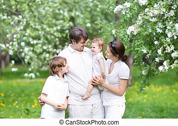 Beautiful young family in a blooming apple tree garden