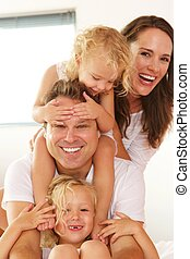 Beautiful young family smiling at home