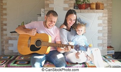 Beautiful young family spending time in the kitchen, father plays the guitar