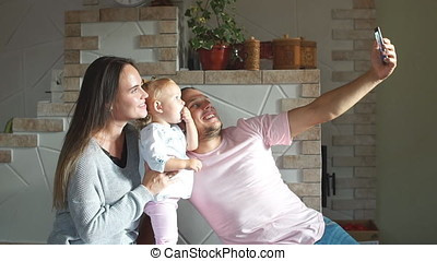 Beautiful young family taking a selfie in kitchen