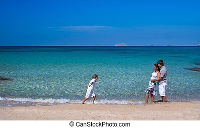 Beautiful young family walking on a tropical beach
