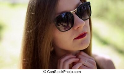 Beautiful young fashion girl in sunglasses with red lips corrects long hair.