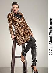 Beautiful young fashion woman sitting on a stool.