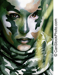 Beautiful young fashion woman with military style clothing and face paint