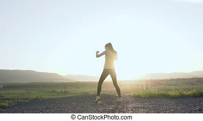 Beautiful young female boxer doing training on the top of mountain in the summer in morning. Angry sports girl doing workout boxing on the outdoors. Sunrise or sunset, kickboxing, boxing, sport, healhy life