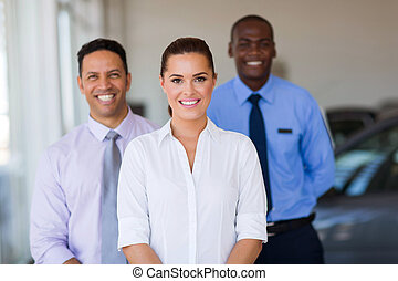 young female car dealer with colleagues on background