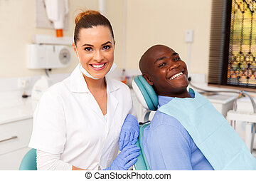 young female dentist and african patient