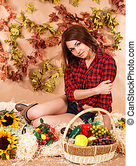 Beautiful young female farmer sitting in a hay with a harvest