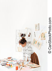 Beautiful young female fashion designer working in studio