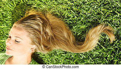 Beautiful young female lying on the grass