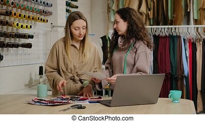 Beautiful young female tailors choosing lining fabric for clothing item from catalog near laptop in workshop
