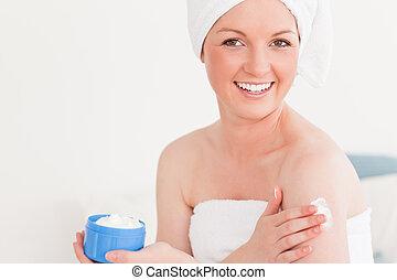 Beautiful young female wearing a towel using skin cream
