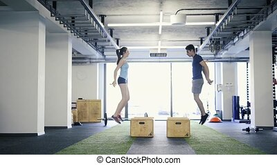 Beautiful young fit couple in gym doing box jumps.