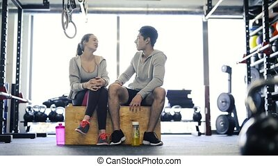 Beautiful young fit couple in modern crossfit gym talking...
