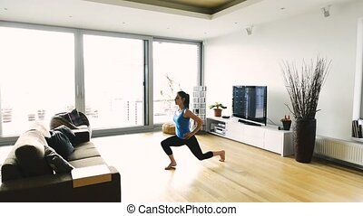 Beautiful young fit woman exercising at home, doing lunges....