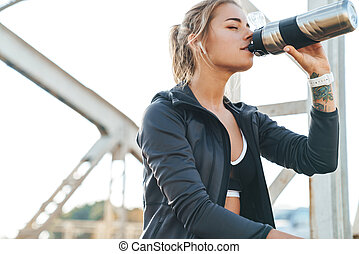 Beautiful young fitness woman drinking water.