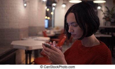 Beautiful young girl chatting online using smartphone app...