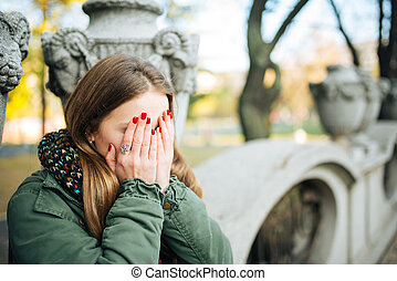 Beautiful young girl covered her eyes.