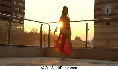 Beautiful young girl dancing on the street of a modern city in the sunset light. She is wearing a red dress. Slow motion.