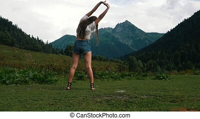 Beautiful young girl doing exercises on the background of amazing nature