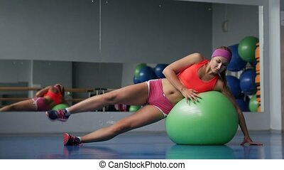 Beautiful young girl doing exercises with fit ball at sport gym.