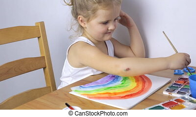 Beautiful young girl draws a rainbow