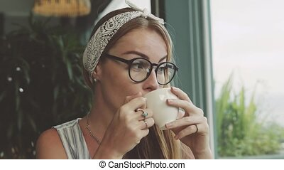 Beautiful young girl drinking coffee and smiling in cafe. .
