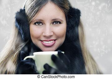 Beautiful young girl drinking coffee or tea