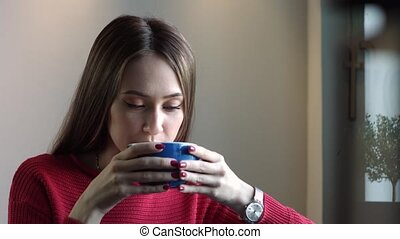 Beautiful Young Girl Drinks Coffee and Smiles