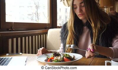 beautiful young girl eats tasty salad