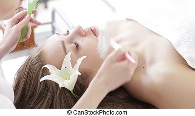 Beautiful young girl getting a facial treatment at the...
