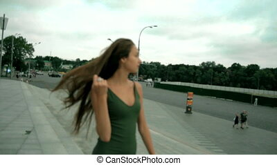 beautiful young girl goes on the city straightens hair