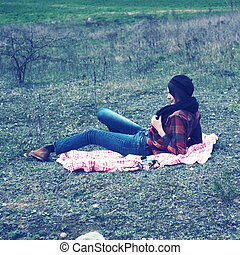 beautiful young girl hipster dreams of lying on a magic meadow in spring. Hipster beautiful girl with the camera in a field in spring