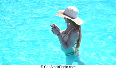 beautiful young girl in a bathing suit and hat stands in the pool holds glasses turns her head forward and smiles