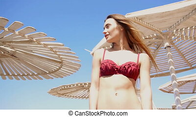 beautiful young girl in a bathing suit stands on the beach umbrellas and looks away