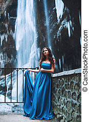 Beautiful young girl in a blue dress standing on the background of a glacier and mountains
