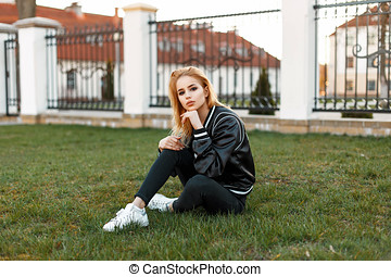 Beautiful young girl in a bomber jacket in black jeans and white shoes sitting on the grass.